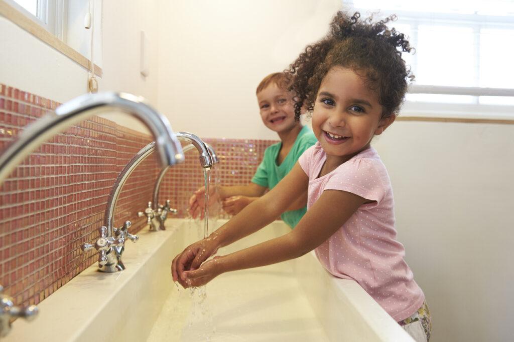 Students At Montessori School Washing Hands In Bathroom